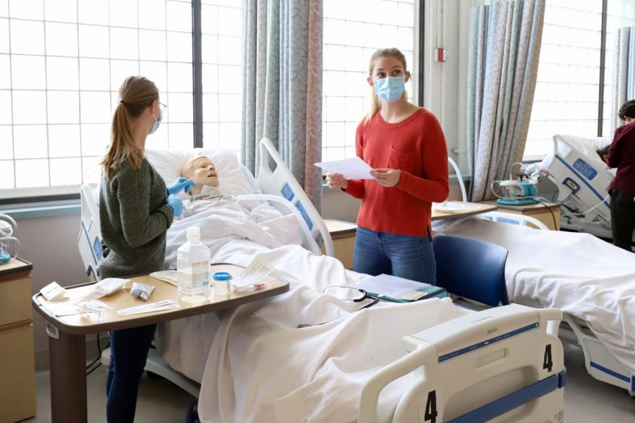 Brea Cook (left), and Cara Christian practice caring for a simulated tracheostomy patient on Feb. 9 2021 at the Nursing Lab in the City College Administration building in Santa Barbara, Calif. Each pair of students work together, learning the entire process of setting up a sterile tray of supplies and changing the dressings where the patient's breathing tube would be placed.