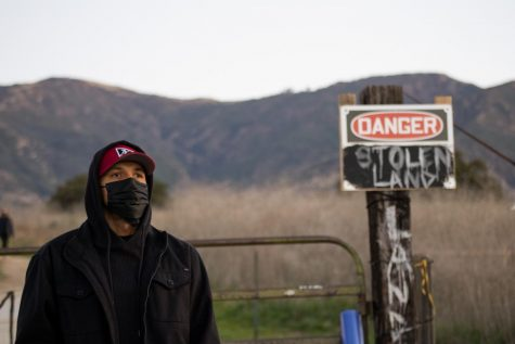 Protester Roy Schulte watches the scene at the sit-in protest on Feb. 26, 2021, at the San Marcos Foothills Preserve in Santa Barbara, Calif. Schulte stayed overnight in support of those trying to protect the land from development.