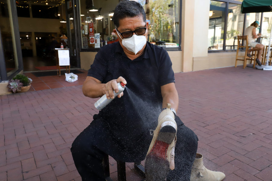 """Lopez preps the suede boot with a protecting spray before taking a 120-grit square of sandpaper to soften the material and remove the grease stain from the boot. Lopez, who worked inside Nordstrom for 26 years shining shoes, said he prefers being outside because of all the people that walk past. """"I like the people,"""" he said. """"I like the talking."""""""