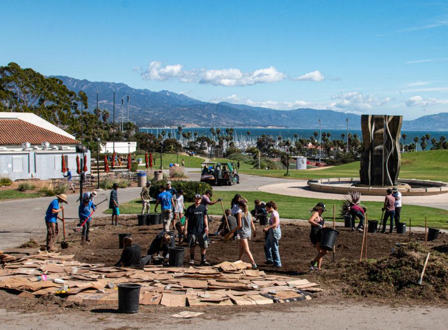Bild mit freundlicher Genehmigung von Professor Adam Green.  Freiwillige arbeiten daran, Pappe über Schmutz zu legen und ihn mit Mulch zu bedecken, um den Boden zu verbessern, während sie am 20. Oktober 2017 am City College in Santa Barbara, Kalifornien, den SBCC Permaculture Garden errichten.