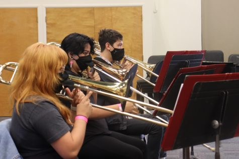 """From left, Andrea Adame, Roxy Hernandez and Koby Pfonner, practice a new song wearing special masks with flaps to prevent the spread of COVID-19 on Thursday, Aug. 26, 2021, in Room 105 in the Drama/Music building at City College in Santa Barbara, Calif. Adame said playing through a mask was doable but """"a little bothersome on fast charts."""""""