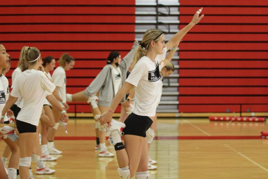 The women's volleyball team warms up before practice on Sept. 21 in the Sports Pavilion at City College in Santa Barbara, Calif. Karoline Ruiz and her teammates are stretching out their hamstrings after doing a multitude of other stretches to avoid injury.