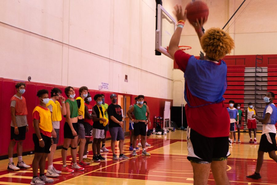 """Coach Devin Engebretsen and the mens basketball team watch their teammate shoot a three-pointer during practice on Sept. 14 at City College in Santa Barbara, Calif. Engebretsen said he has been prepping his players to be ready to """"catch and shoot"""" for when the opportunity arises."""