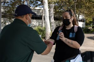 City College employee Mauro Escamilla applies a wristband to first-year international student Sarah Provoost on Thursday, Sept. 2, 2021 at City College in Santa Barbara, Calif. Students must fill-out a survey online or in-person and receive a wristband prior to entering buildings on campus.